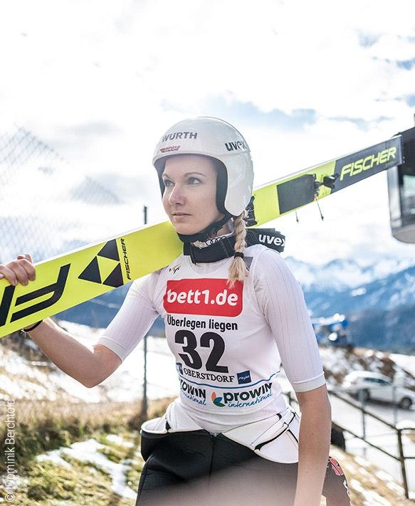 Foto: Una saltadora de esquí se pone los esquís al hombro; publicidad de bett1 en su maillot.