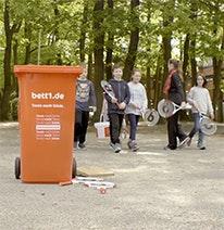 Foto: En primer plano una papelera roja, al fondo niños con raquetas de tenis.