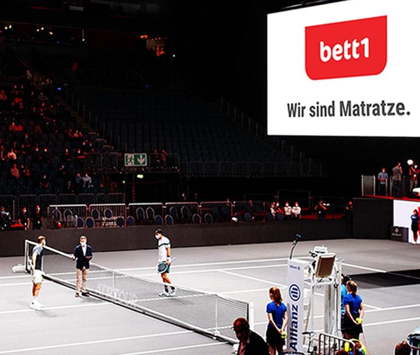 Foto: En el bett1HULKS dos jugadores se enfrentan en la red, el tablero iluminado en la arena muestra el eslogan de bett