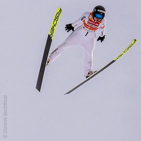 Foto: Una saltadora de esquí en el aire; publicidad de bett1 en su maillot.