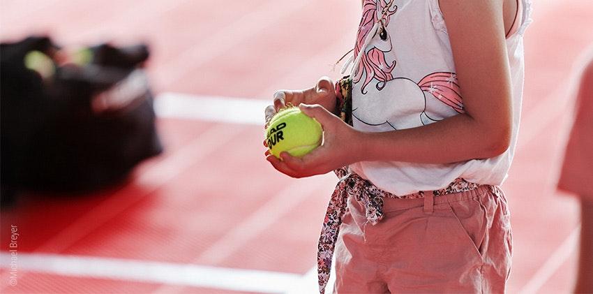 Foto: Un niño sostiene una pelota de tenis en la mano.