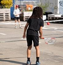 Foto: Un niño juega una pelota de tenis roja sobre la red con otro niño.